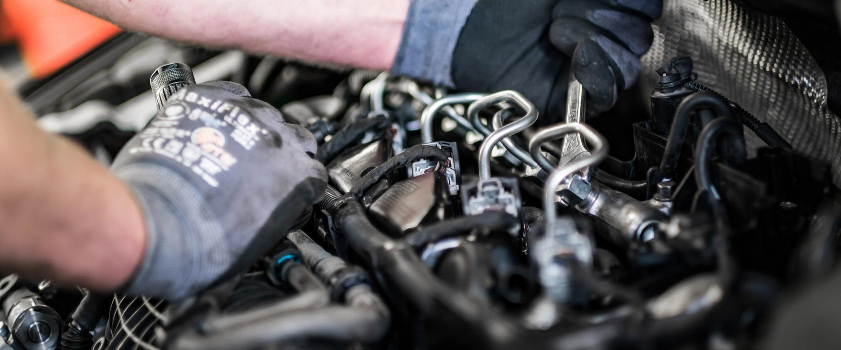 En mekaniker som skrur på motoren i en bil