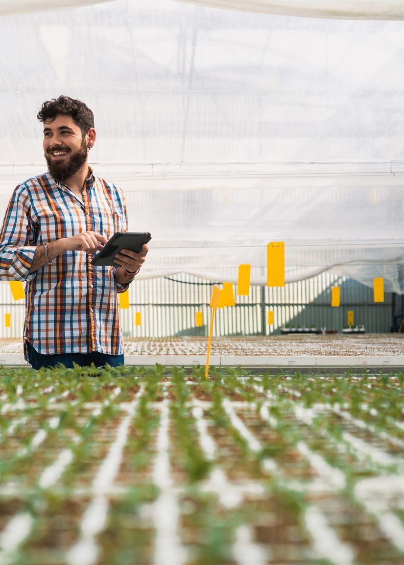 Photograph of a smiling farmer using digital technology in a greenhouse
