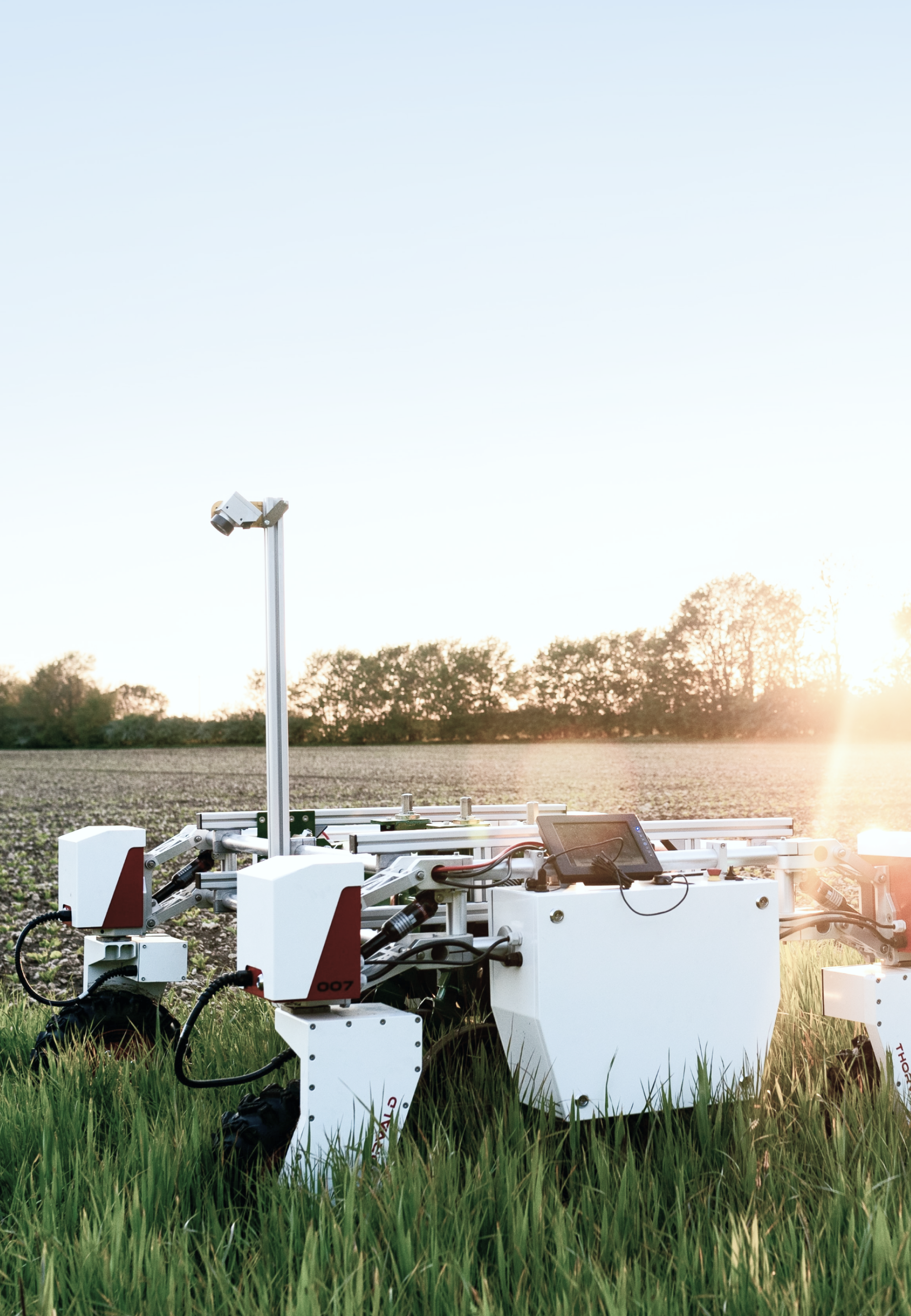 A large wheeled scanning and farming robot in a large green field