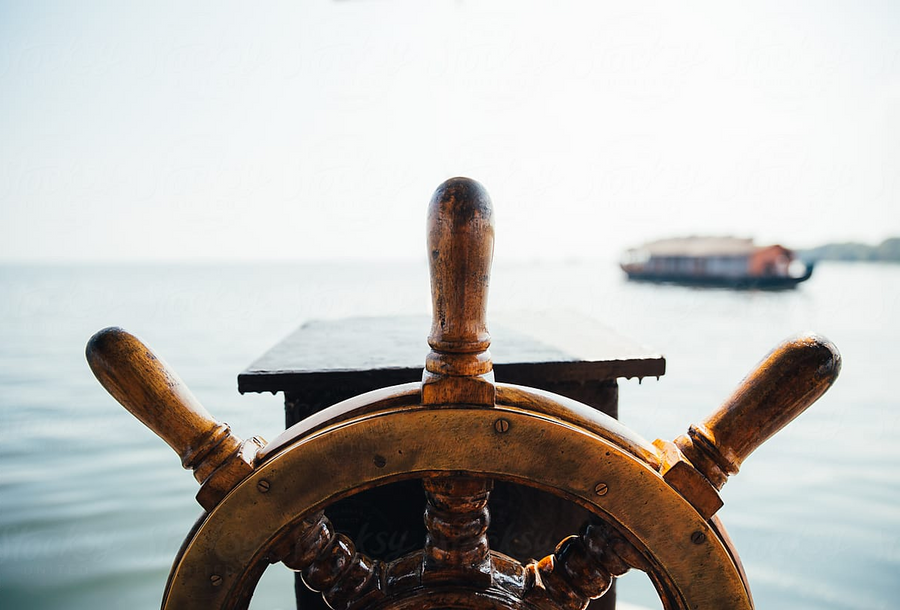 A boat steering wheel in front of the sea