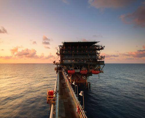 Bilde av en oljeplattform i solnedgang.