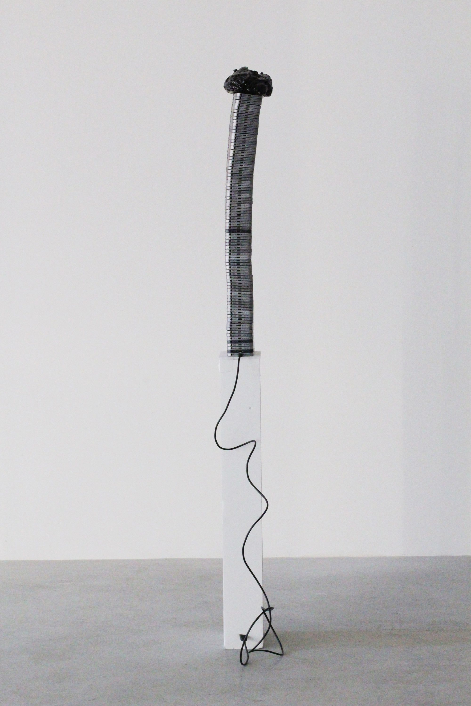 Untitled (Too Thick) | 2018 | Aluminum phone casings, silicone, polyurethane, asphalt, wood, Lightning to USB cord