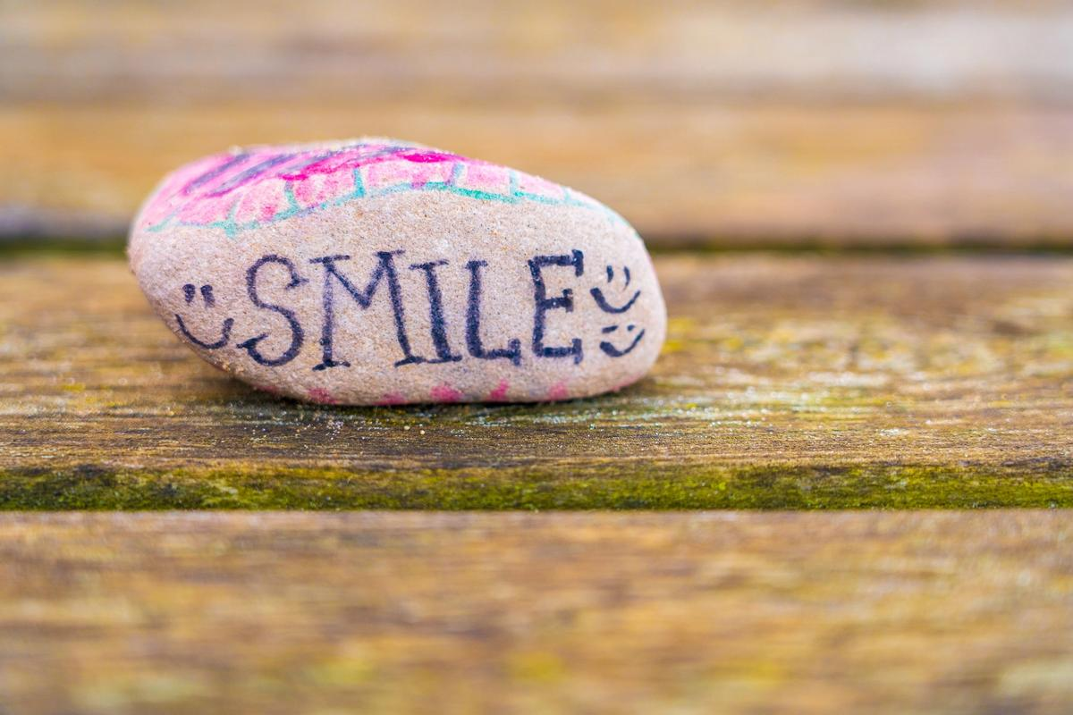 A stone with the words 'Smile' drawn on in pen