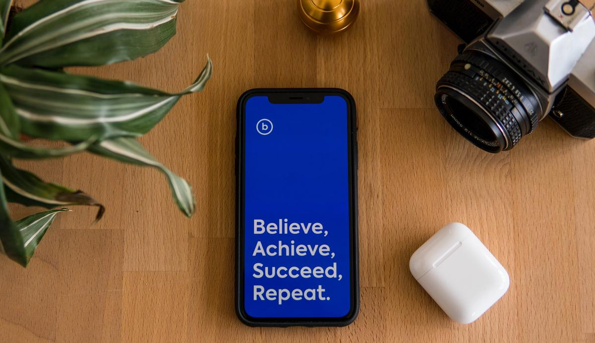 An iphone with a blue screen featuring the words: 'Believe, Achieve, Succeed, Repeat.'