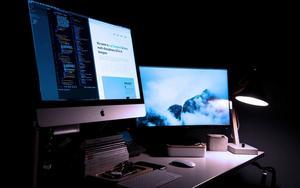 Two desktop mac screens against a dark background
