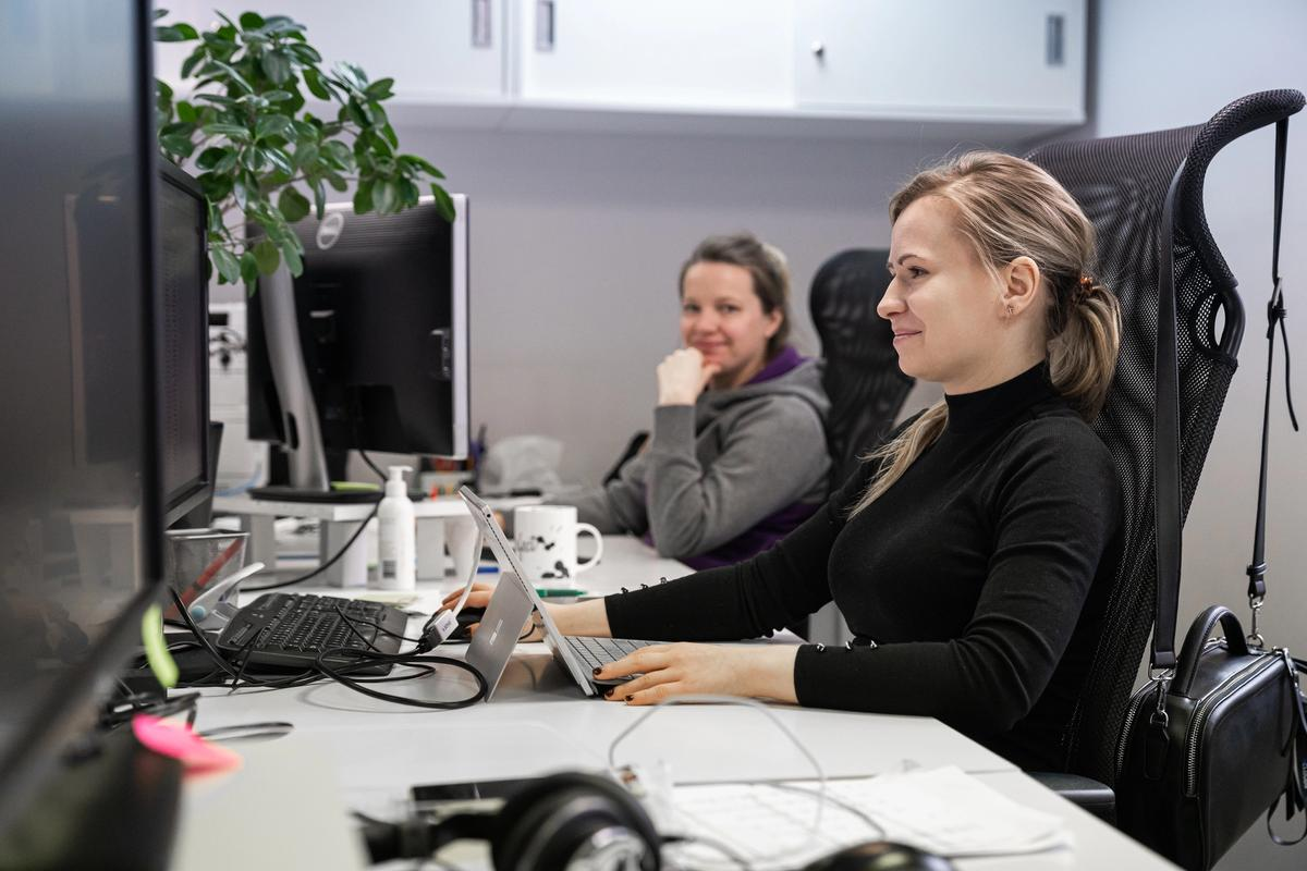 A girl with long hair sitting at an office desk coding.