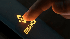 A finger pressing the entrance screen of the Binance App