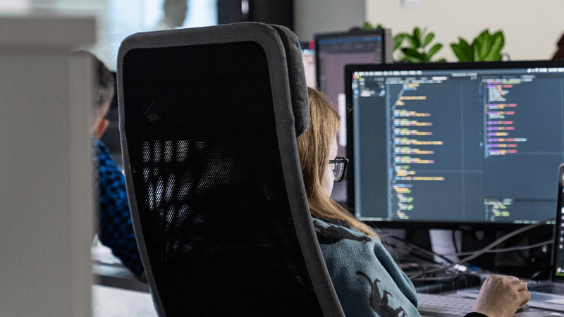 Woman working at a desk with code on a dark screen