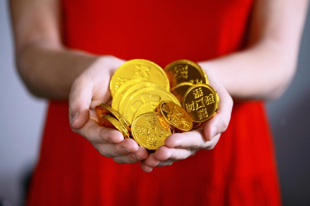 Woman in red dress holding a handful of gold coins