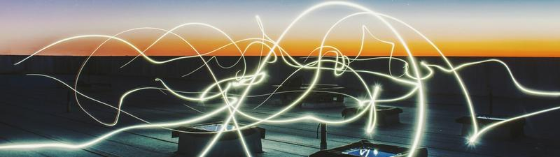 Electric message currents travelling through the air from one device to another against the backdrop of a sunset.