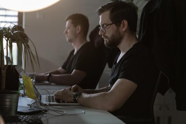 Two developers working on laptops at an office desk