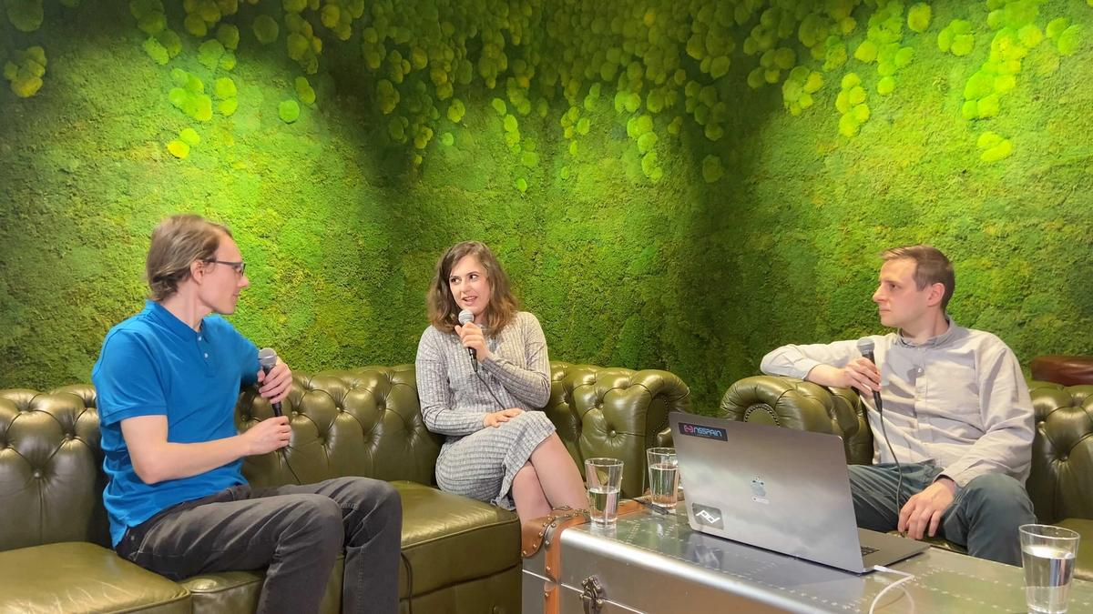 Two guys and a girl sitting at a desk in an office recording a podcast