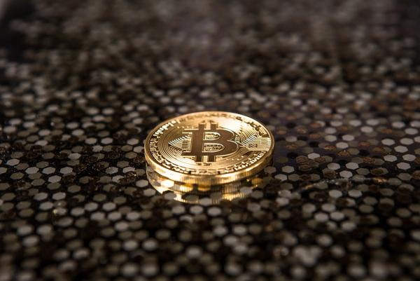 A single bitcoin on a brown and black speckled background