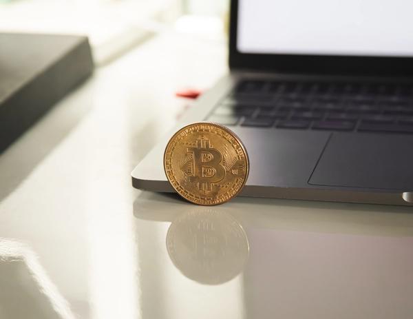 A single BitCoin balanced against the edge of a laptop