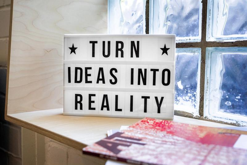 Image of a sign on a sunny windowsill saying 'Turn Ideas into Reality'