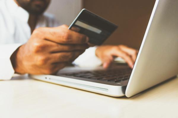 User with a debit card using a laptop
