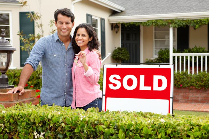 Couple in front of newly bought house using a VA Loan.