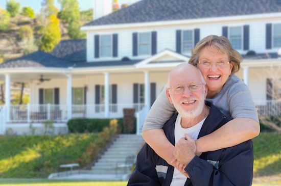 Senior couple standing in front of new house.