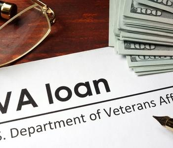VA loan document with pen and money on the table.