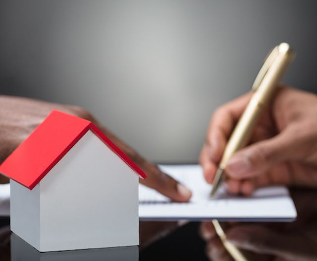 Signing VA loan documents with a house concept in table