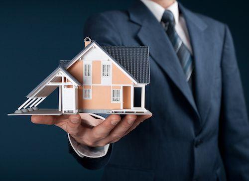 Man holding a miniature house.
