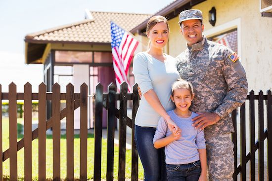 Family of military standing in front of new house.