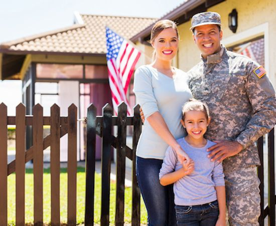 Family of a veteran standing outside their house.