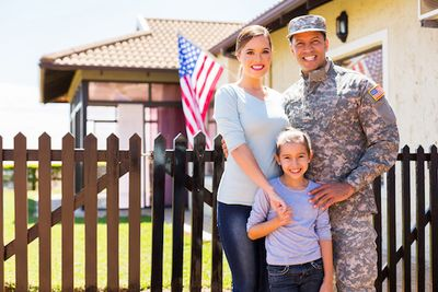 Military with his family standing in house acquired using a VA loan.