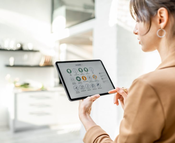 Woman controlling smart home using a gadget.