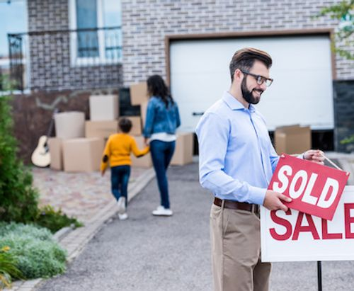 Man placing sold sign to house listing.