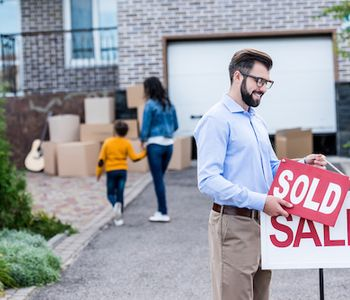 Man placing sold sign on home listing.
