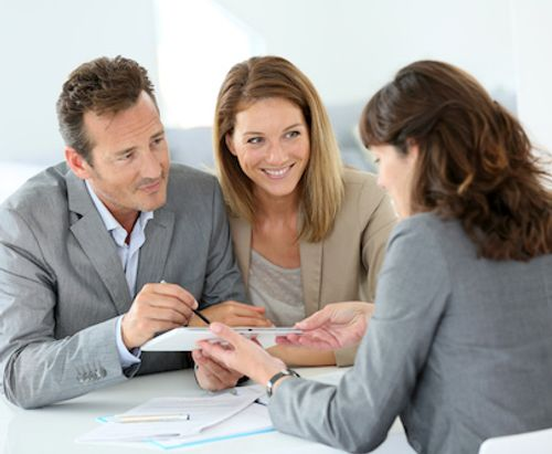 Couple discussing home mortgage with VA loan specialist.