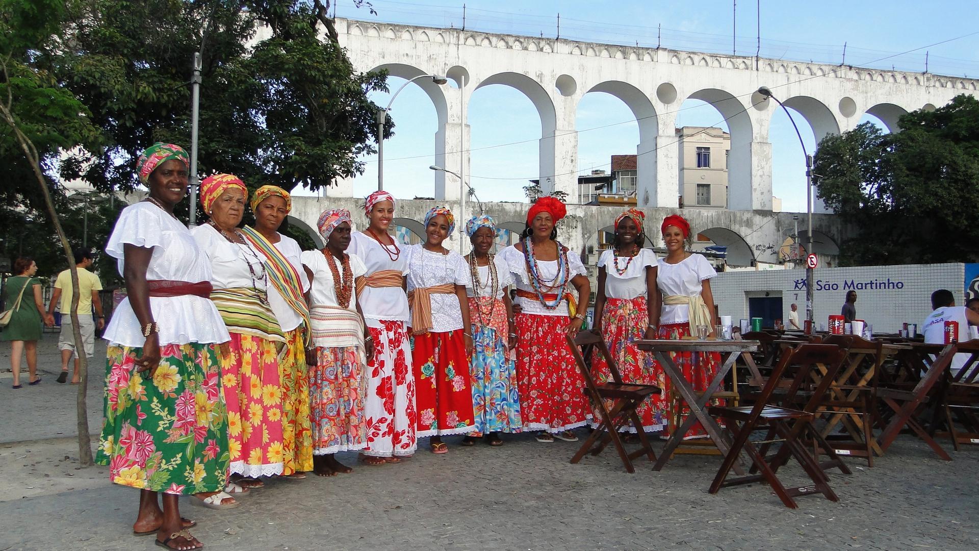 Ganhadeiras de Itapuã posicionadas uma ao lado da outra com os Arcos da Lapa, Rio de Janeiro, ao fundo
