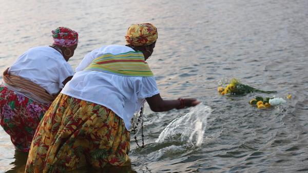 Duas Ganhadeiras de Itapuã lançam oferendas de flores ao mar