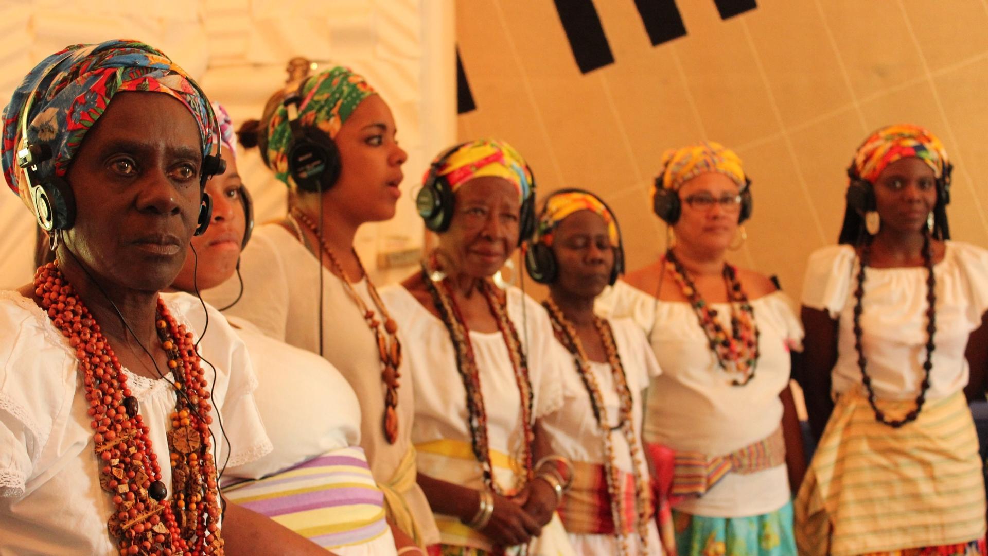 Ganhadeiras de Itapuã com fones de ouvido no Estúdio Coaxo de Sapo