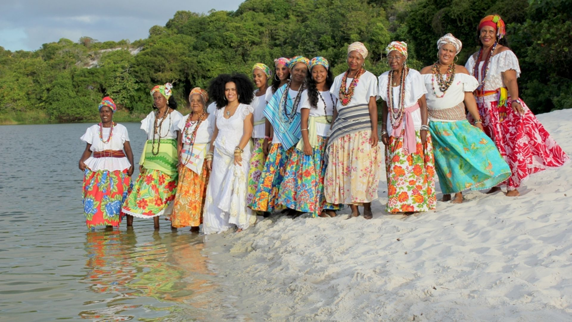 Ganhadeiras de Itapuã com a cantora Mariene de Castro sentadas na areia da Lagoa do Abaeté