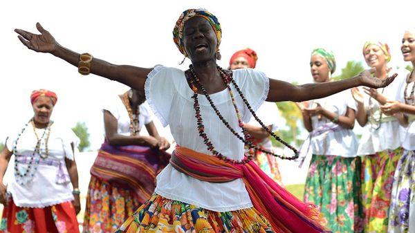 Ganhadeira Raquel das Virgens aparece em primeiro plano, cantando de braços abertos, com outras ganhadeiras em segundo plano