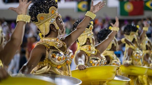 Mulheres negras vestidas de dourado seguram bacias douradas no desfile da escola Unidos da Viradouro