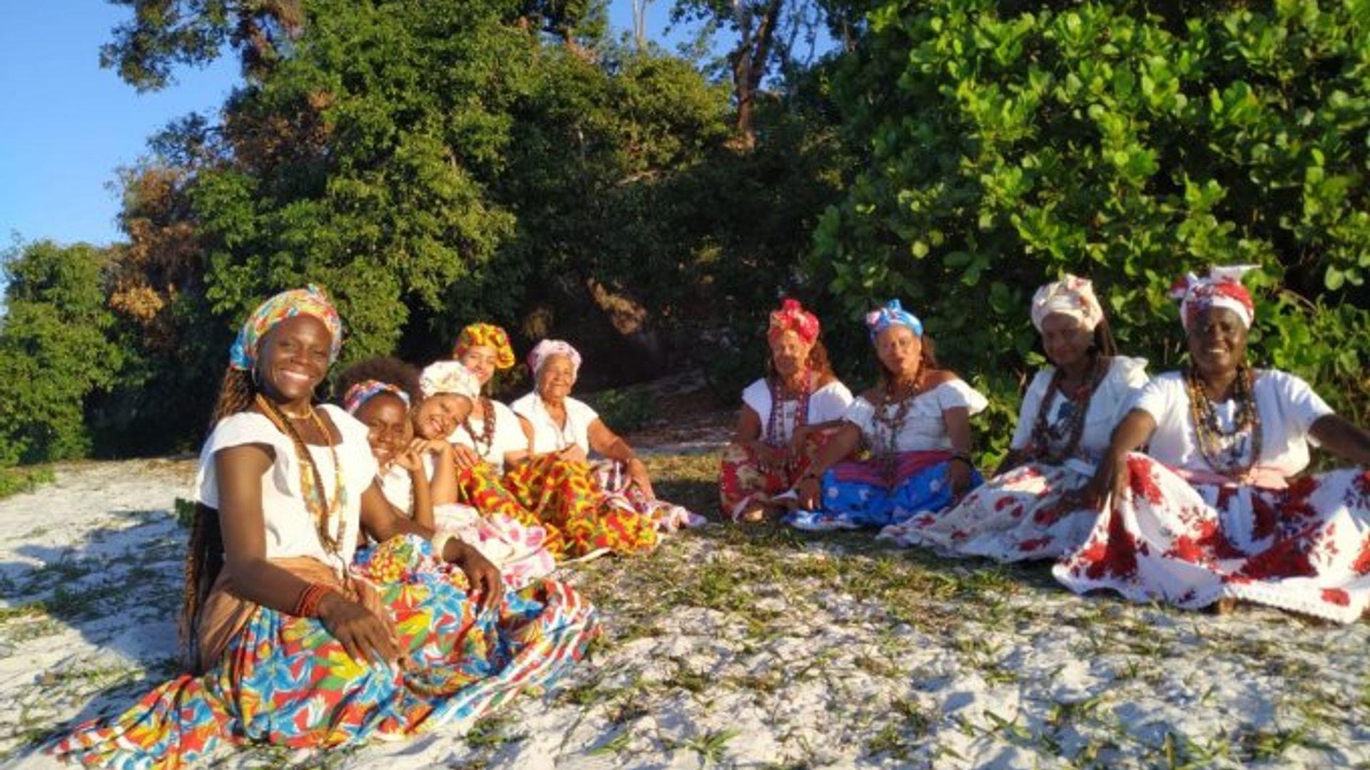 Ganhadeiras de Itapuã sentadas em semi-círculo na areia, sorriem para a câmera.