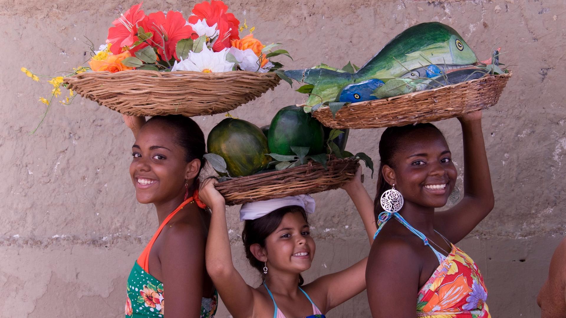 Três meninas adolescente com cestos sobre a cabeça lembram o trabalho das ganhadeiras
