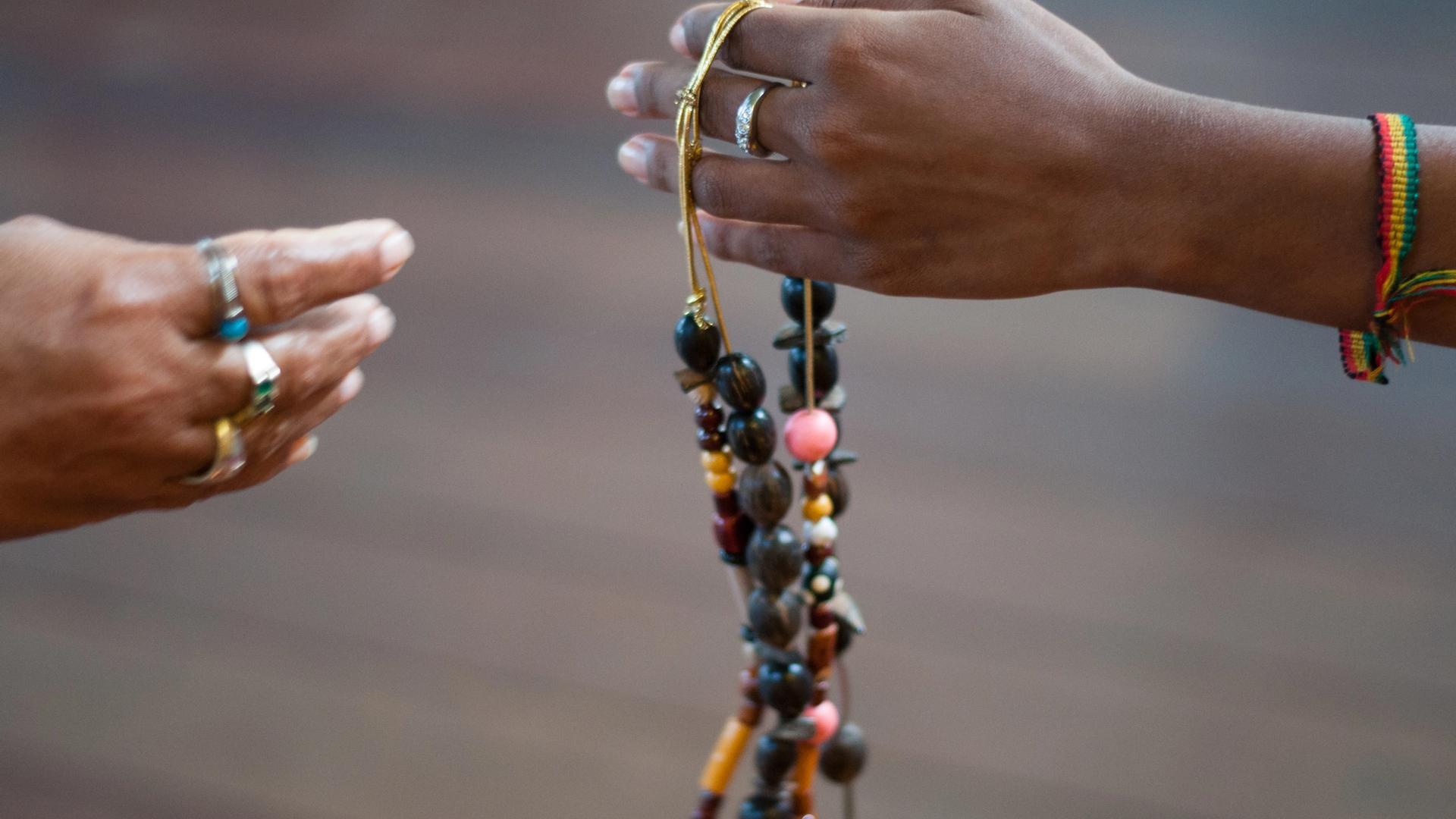 Uma mão se estende para outra oferecendo um colar de contas.
