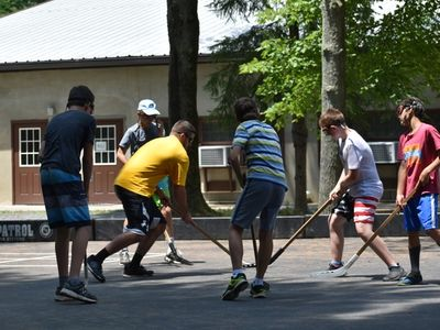 teens playing street hockey at Rambling Pines Day Camp