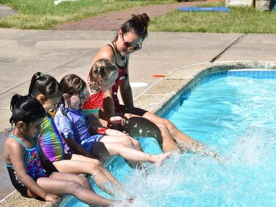 kids practicing swim moves on the side of the pool with swim instructor at Rambling Pines Day Camp