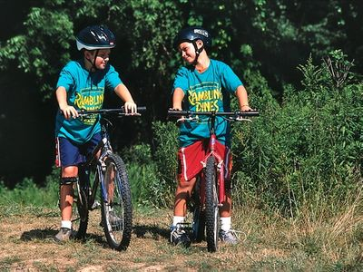two campers riding bikes together wearing helmets and Rambling Pines Day Camp t-shirts