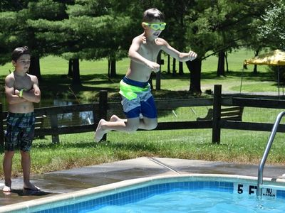 child jumping in the pool at Rambling Pines Day Camp