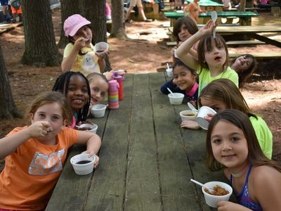 kids sitting around a picnic table eating and smiling at the camera at Rambling Pines Day Camp