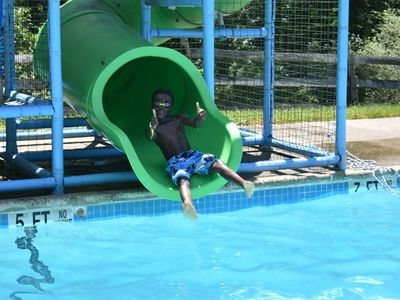 camper going down a water slide at Rambling Pines Day Camp