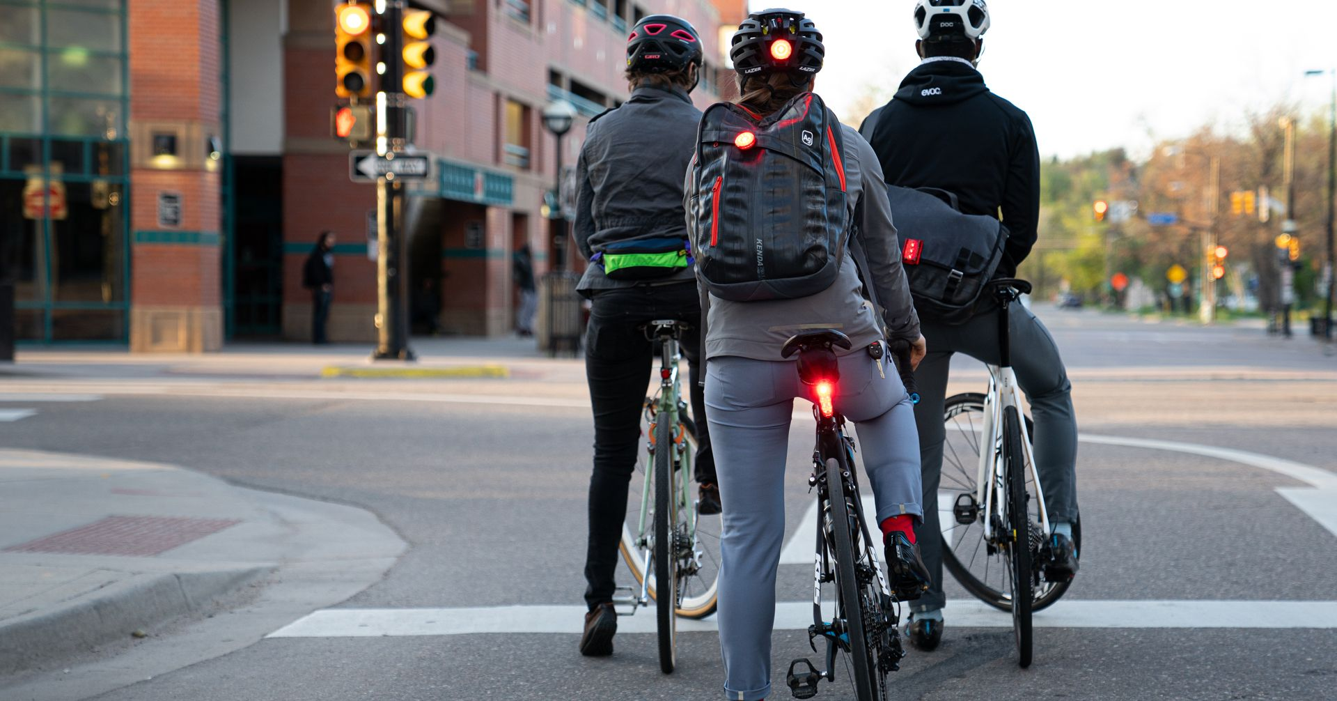 A group of cyclists at the traffic lights with rear bike lights on