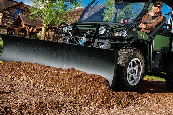 Man spreading dirt with a front blade on his XUV Series Gator