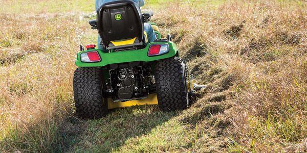 Man cutting tall grass with John Deere lawn mower